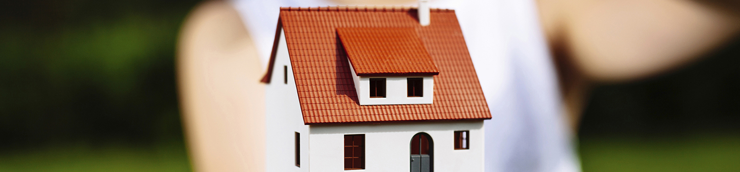 Home insurance concept. Photo of a woman holding a miniature house and protecting it with her hand